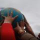 Children's hands raising a globe in the air.
