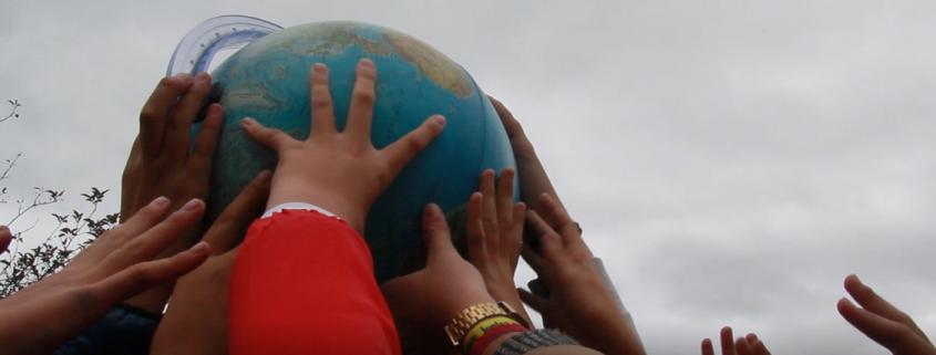 Children's hands raising a globe in the air.