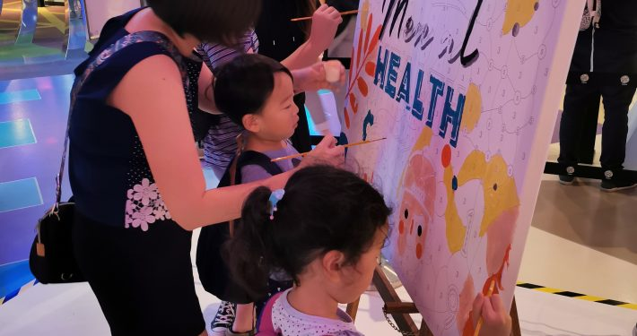 Visitors participate in a painting session for mental health awareness.